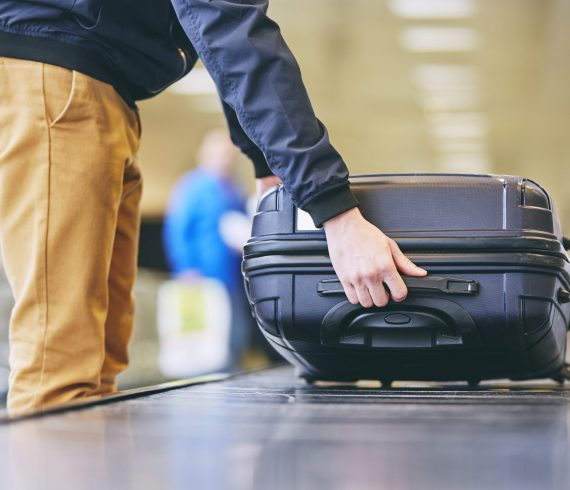 Traveler picking up suitcase from baggage claim in airport terminal.