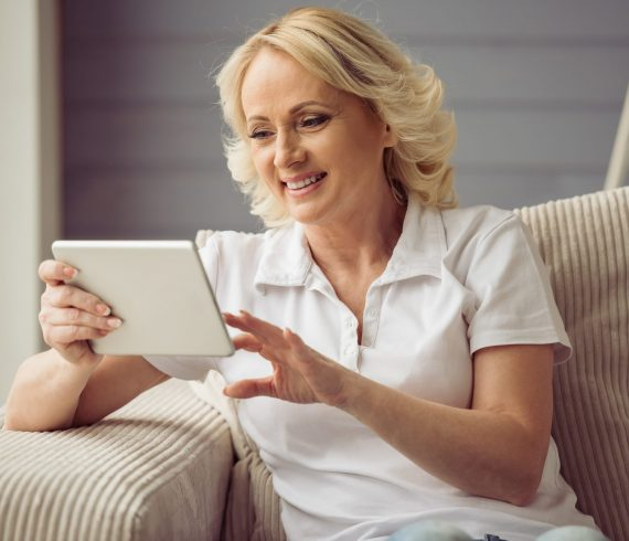 Beautiful old woman in casual clothes is using a tablet and smiling while sitting in armchair at home