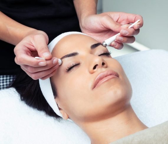 Shot of cosmetologist making the eyes contour therapy for rejuvenation to woman on the spa center.